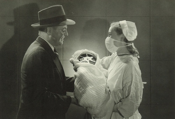 a nurse hands over a swaddled baby with a film reel for a head